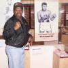 Spinks raises a fist next to the Muhammad Ali exhibit.